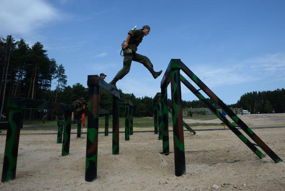 Um participante das competições Pelotão de Tropas Aerotransportadas passa por uma pista de obstáculos no polígono.