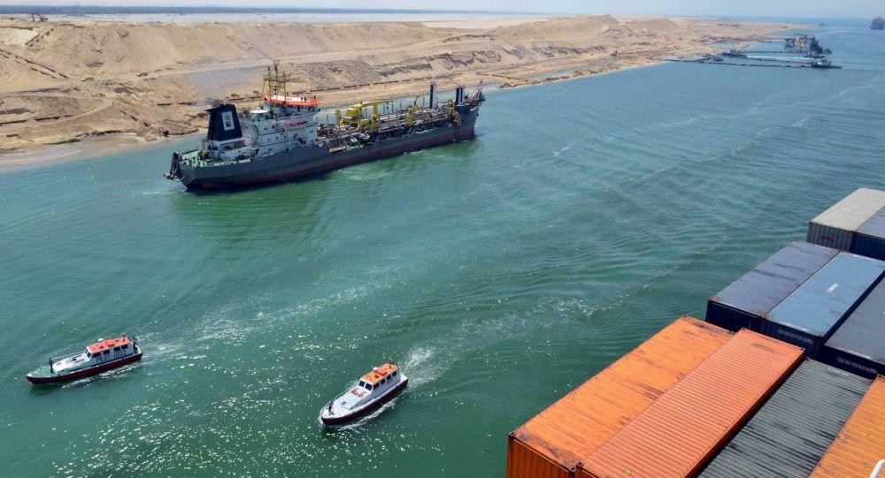 Um navio de carga navega na nova via do Canal de Suez em Ismailia