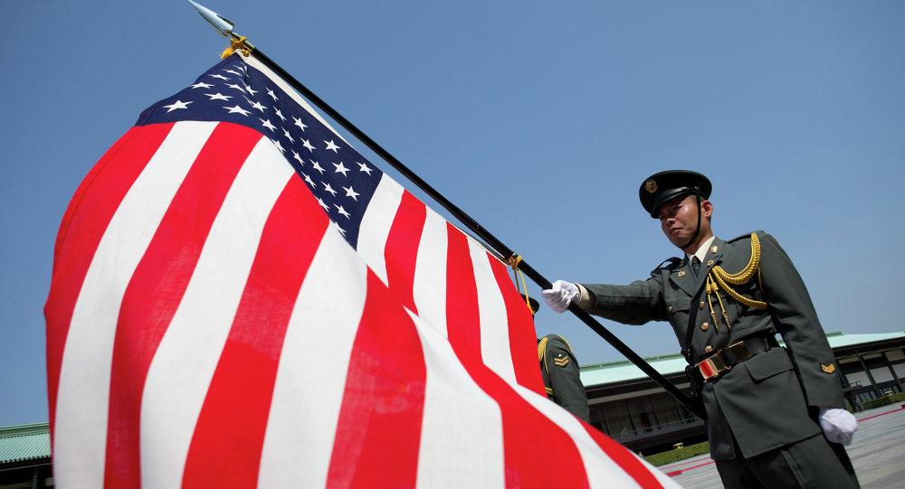 Soldado japonês segura bandeira americana em cerimômia na cidade de Tóquio.