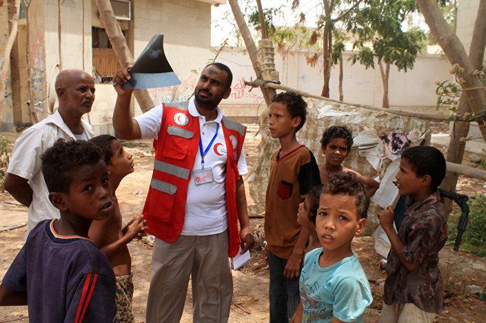 Um representante da Cruz Vermelha com um grupo de crianças iemenitas evacuadas na cidade portuária de Aden, no sul do país