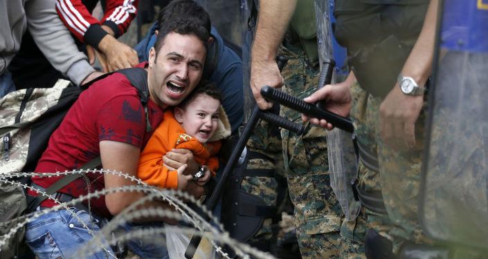 Imigrante com criança durante conflito entre imigrantes e polícia da Macedônia