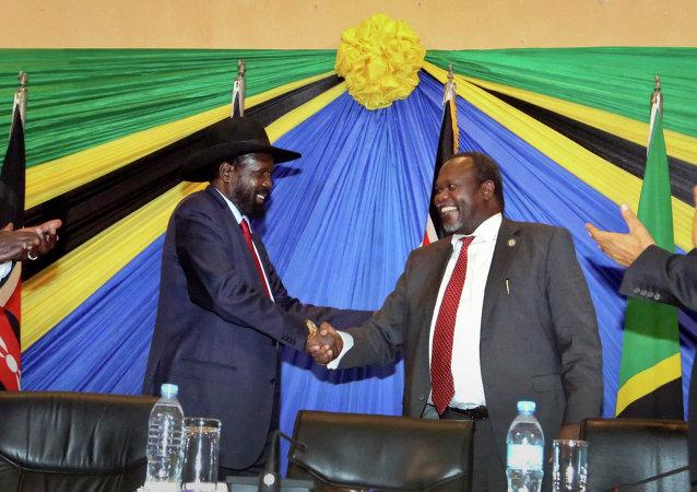 Presidente do Sudão do Sul, Salva Kiir, à esquerda, aperta a mão do líder rebelde e ex-vice presidente do país, Riek Machar, à direita, em Janeiro de 2015, após assinar um dos primeiros acordos que pavimentaram a estrada para o fim da guerra civil