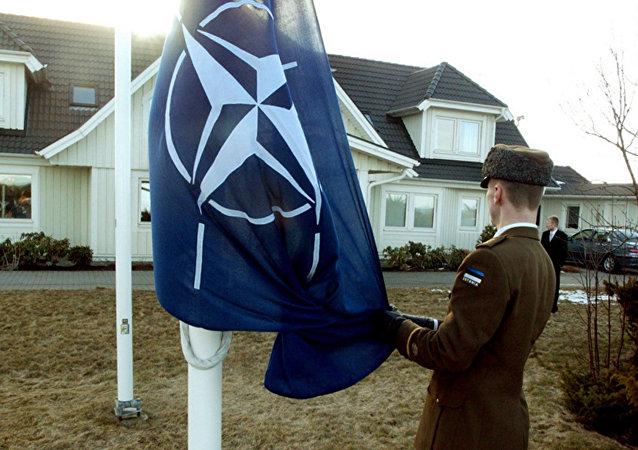 Soldado estoniano iça a bandeira da OTAN em frente da casa do ex-presidente da Estônia, Lennart Meri, na cidade de Tallinn. 29 de março de 2004.
