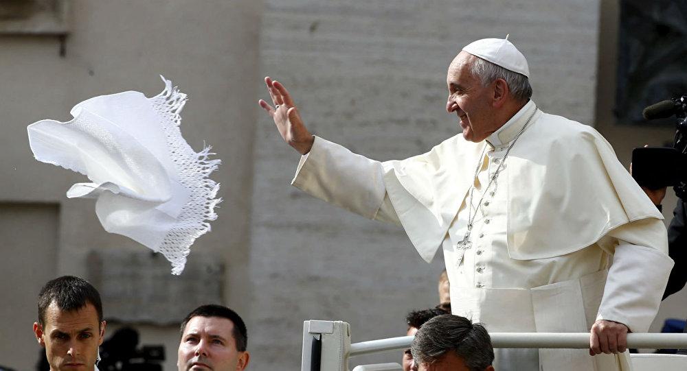 Papa Franciso tenta pegar um lenço jogado por um fiel na Praça São Pedro.