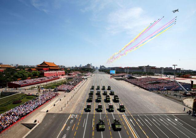 Uma aeronave e veículos militares do Exército de Libertação Popular da China passam pela praça de Tianamen