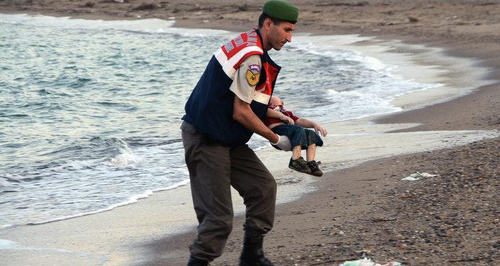 Um policila turco segura rapaz sírio afogado perto de Bodrum