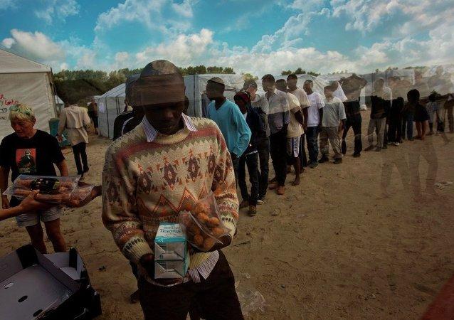 Imigrantes recebem alimentos em campo de refugiados da cidade de Calais, no norte da França