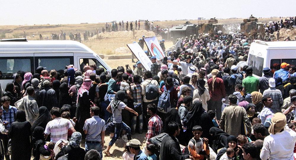 Refugiados sírios à espera de transporte após atravessar a fronteira com a Turquia da cidade síria de Tal Abyad (arquivo)