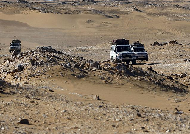 Veículos cruzam o deserto no Egito na mesma região em que o Exército egípcio atacou um comboio de turistas por engano.