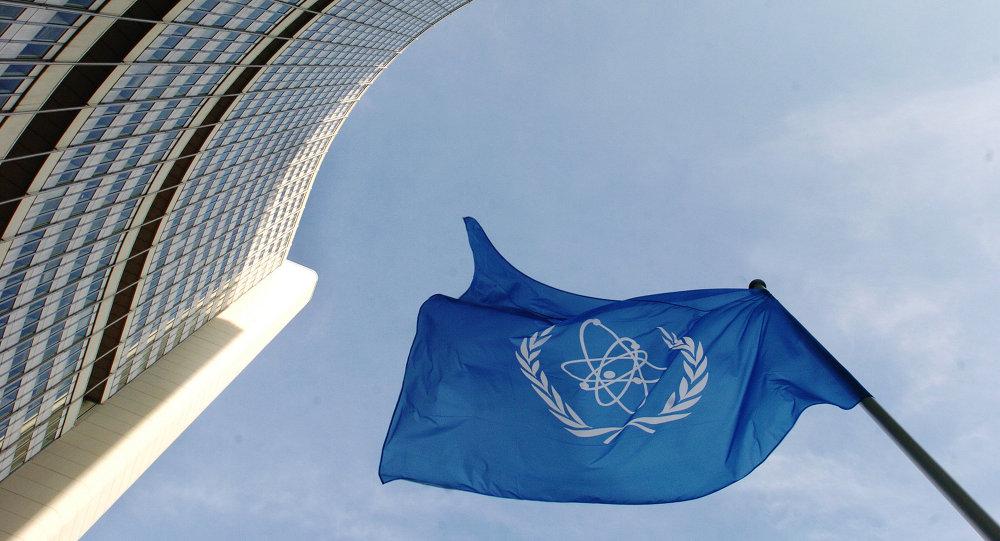 Bandeira da Agência Internacional de Energia Atômica em frente da sede da organização em Viena