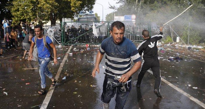 Impedidos de entrar na Hungria, refugiados atiram objetos contra a polícia húngara, que responde com gás de pimenta e canhões de água