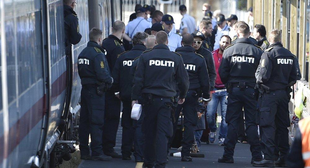 Polícia dinamarquesa junto a um trem com refugiados sírios e iraquianos