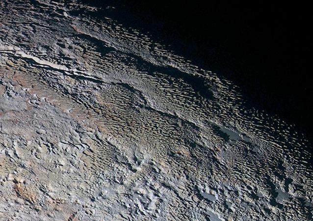 As montanhas de textura esquisita nomeadas informalmente Tartarus Dorsa mostram as cores do planeta anão.