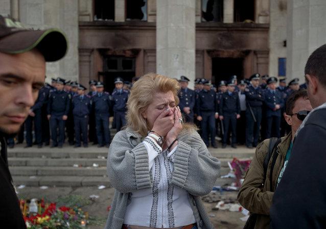 Uma mulher chora em Odessa, na Ucrânia, onde mais de 50 pessoas morreram tentando escapar durante confrontos em 2014