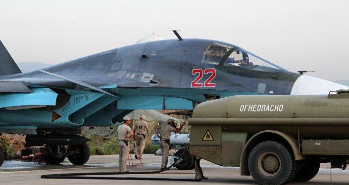 Técnicos reabastecem um Su-34 no aeroporto de Hmeimim, perto de Latakia, na Síria.