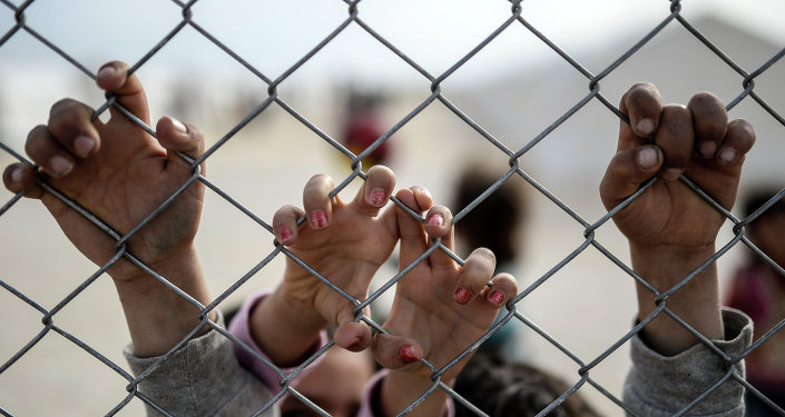 Mãos de crianças curdas sírias em campo de refugiados