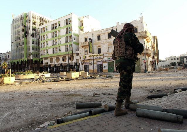 Soldado l[ibio leal ao governo internacionalmente reconhecido patrulha uma rua na cidade costeira de Bengazi em 28 de fevereiro de 2015