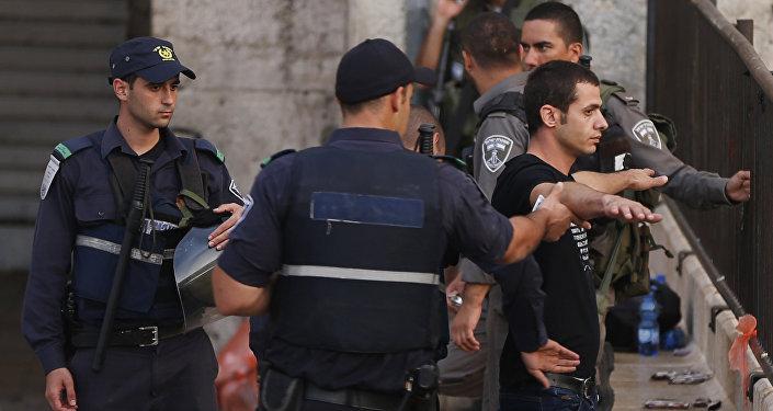 Policiais israelenses estão revistando um jovem palestiniano próximo à entrada à Cidade Antiga em Jerusalém Oriental, 13 de outubro de 2015