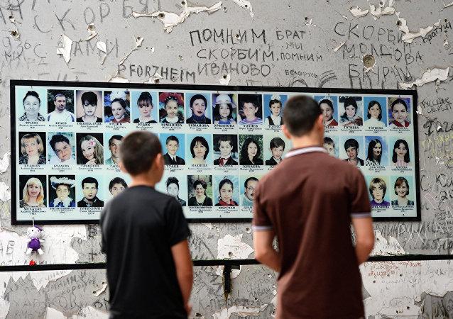 Habitantes locais perto da placa memorial no dia de cerimônia em homenagem das vítimas do atentado na escola em Beslan