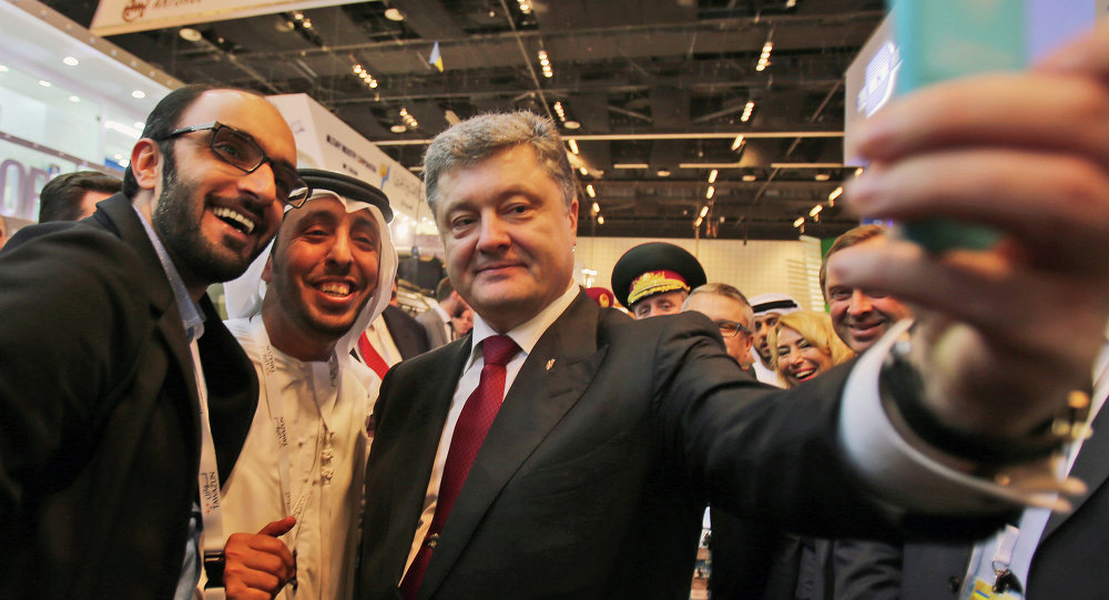 Ukrainian President Petro Poroshenko takes a selfie with an Emirati media representative at the International Defence Exhibition and Conference, IDEX, in Abu Dhabi, United Arab Emirates
