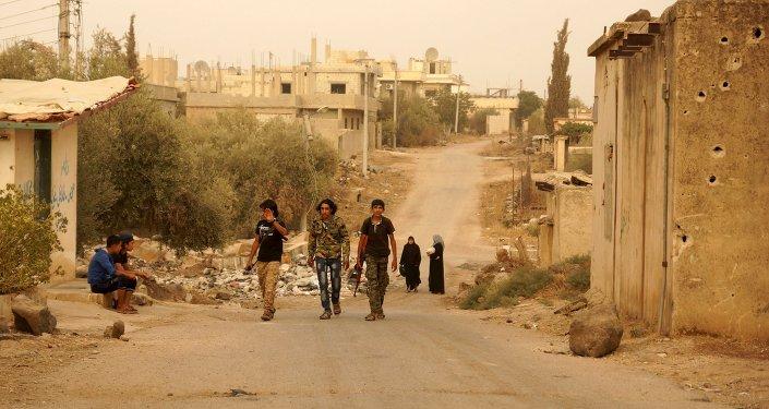 Combatentes do Exército Livre da Síria caminham armados na cidade de Deraa