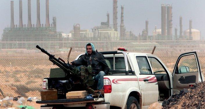 Rebelde em frente à refinaria de petróleo, após captura pelas forças opositoras ao governo da cidade de Ras Lanouf, no Leste da Líbia