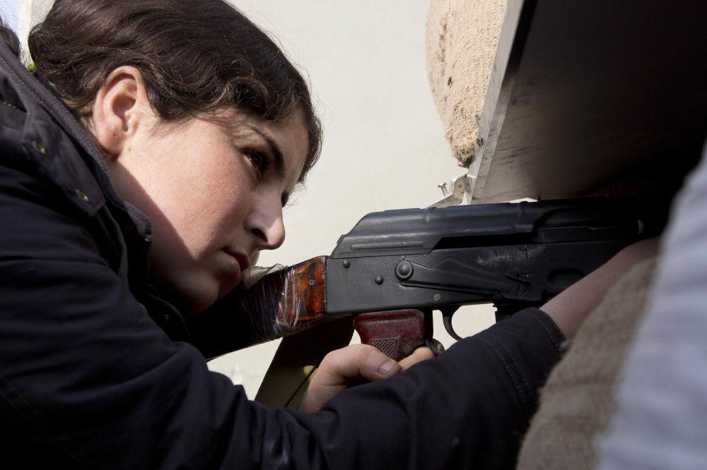 Uma miliciana curda faz pontaria, alvejando os terroristas do Estado Islâmico.