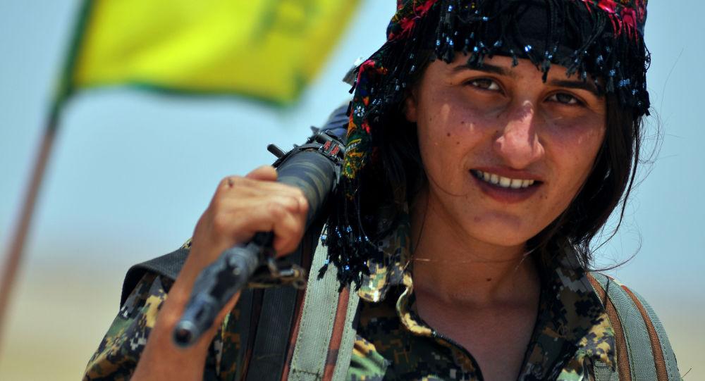 Uma miliciana da Unidade de Proteção do Povo (YPG) curda posa para uma foto com sua arma, na cidade síria de Ain Issi, cerca de 50 quilômetros norte de Raqqa, o chamado capital do Estado Islâmico.