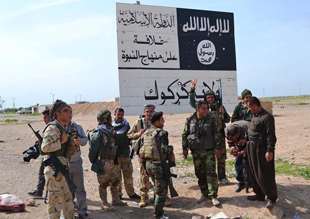 Combatentes peshmerga do Curdistão iraquiano ao lado de uma placa do Daesh