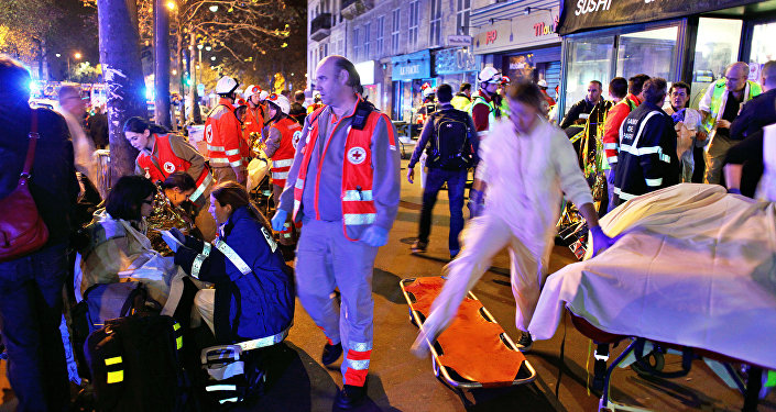 Pessoas descansam após evacuação da casa de shows Bataclan em Paris, 13 de novembro de 2015