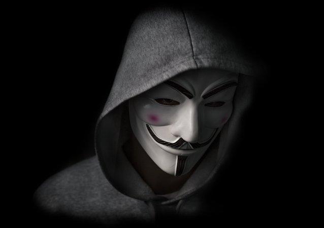 Homem usa uma máscara de Guy Fawkes, símbolo do grupo de hackers Anonymous