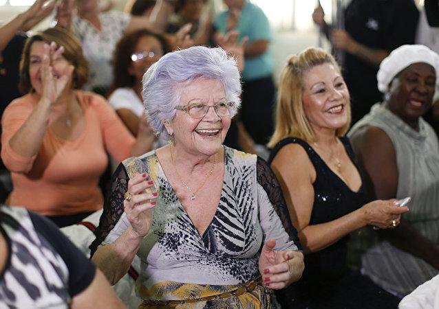 Uma mulher aplaude o seu namorado idoso que participa no concurso Homem mais bonito idoso em São Paulo. 6 de agosto, 2015