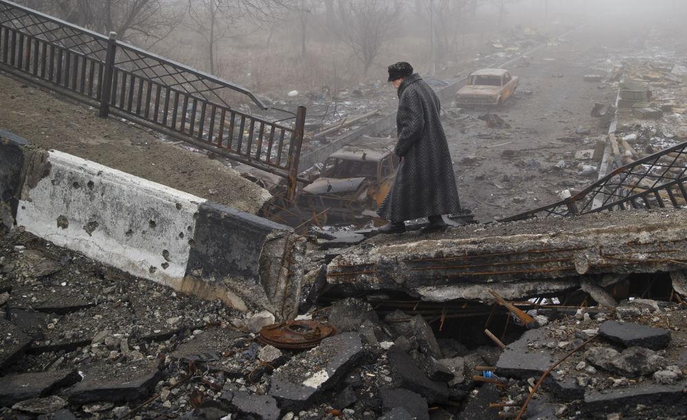 Mulher idosa atravessa uma ponte destruída em Donetsk
