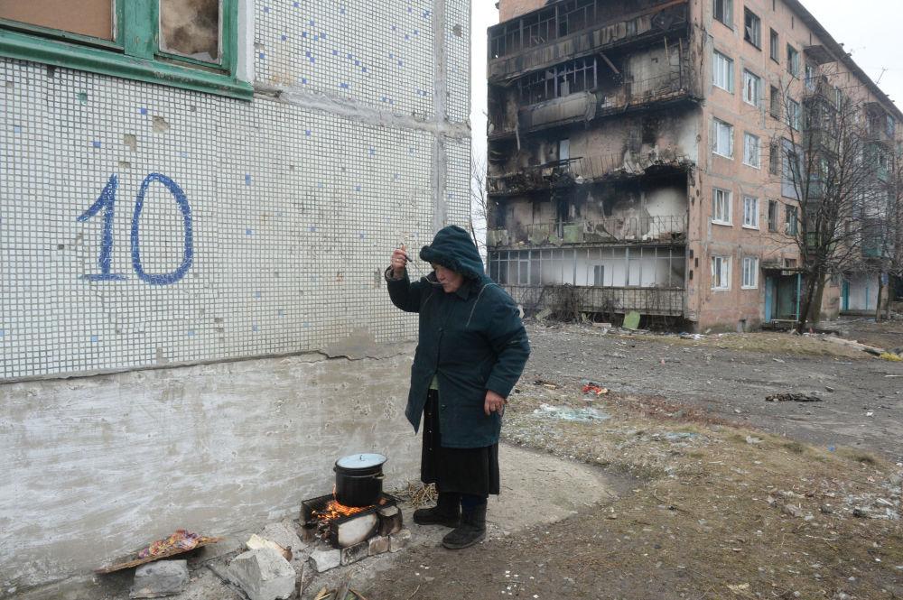 Mulher usa fogueira para preparar comida em Debaltsevo