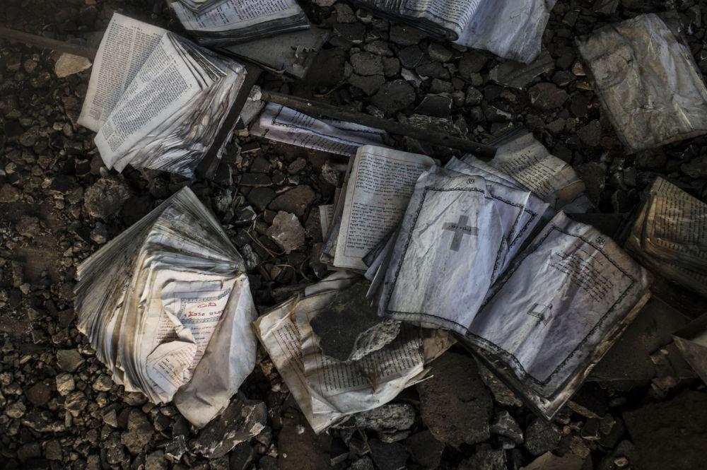 Livros religiosos queimados pelo Daesh em vilarejo cristão na província de Al-Hasaka, nordeste da Síria