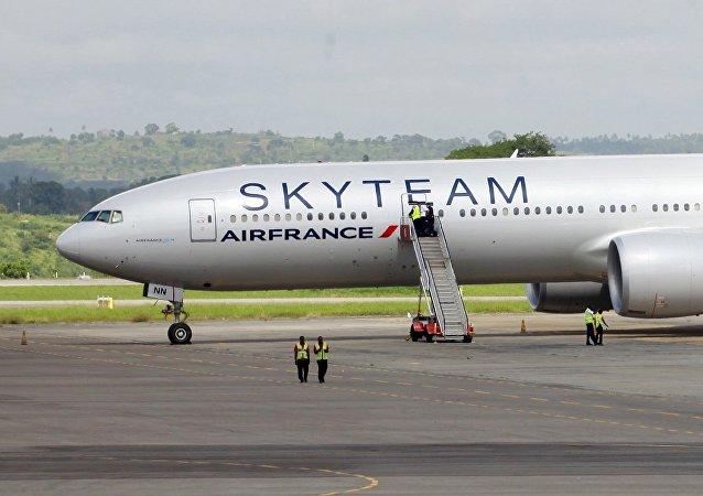 Trabalhadores do aeroporto ficam perto da aeronaves Boeing 777 da Air France que fez um pouso de emergência no Aeroporto Internacional Moi na cidade costeira do Quênia de Mombasa, 20 de dezembro de 2015