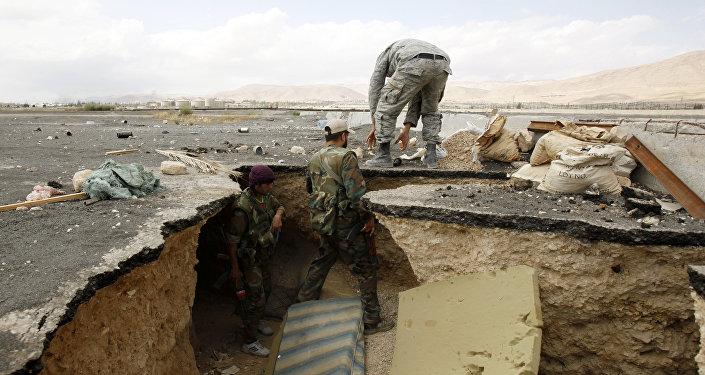 Forças do governo sírio saem de um túnel, segundo as informações recebidas anteriormente, usado por combatentes rebeldes em 28 de setembro de 2014 depois que assumiram o controle da cidade de Adra al-Balad, nos arredores da capital Damasco