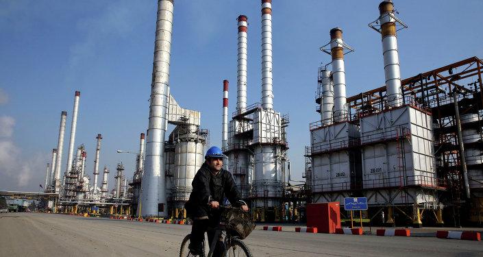 Funcionário do setor petrolífero iraniano vai de bicicleta  perto da refinaria petrolífera no sul de Teerã, Irã