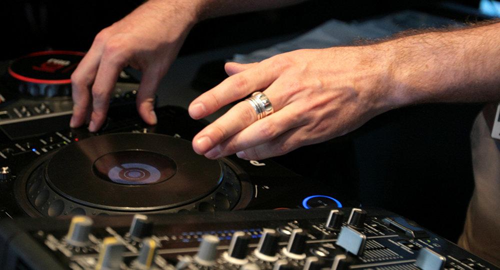 Mãos do DJ que toca uma composição musical