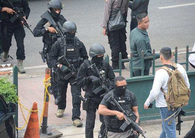 Policiais armados indonésios chegam para o local dum dos atentados em Jacarta, Indonésia, 14 de janeiro de 2016