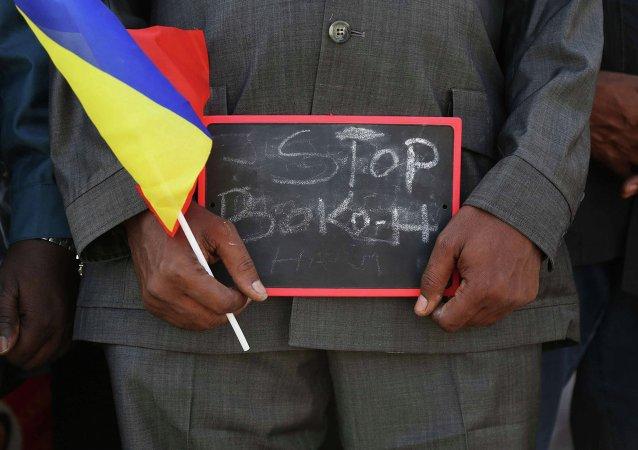 Homem segura uma placa pedindo que o Boko Haram seja detido