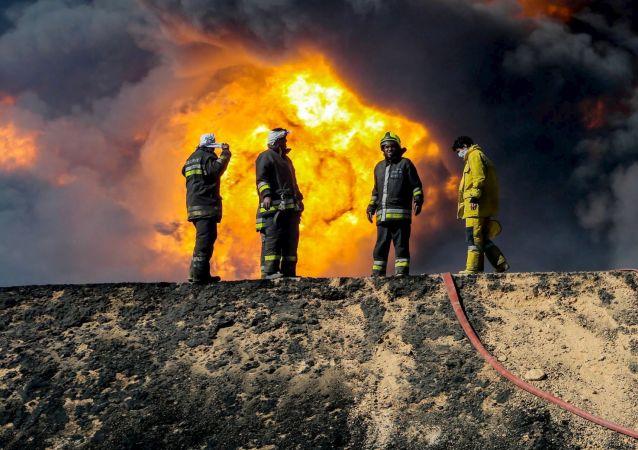Bombeiros combatem o incêndio de um depósito de petróleo em Ras Lanuf, na Líbia, em 6 de janeiro de 2016