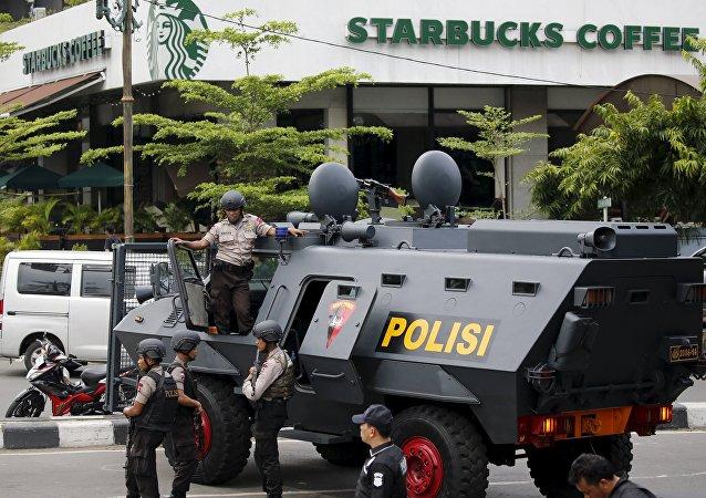 Policiais indonésios armados e um carro blindado no local da explosão que teve lugar em Jacarta, Indonésia, 14 de janeiro de 2016