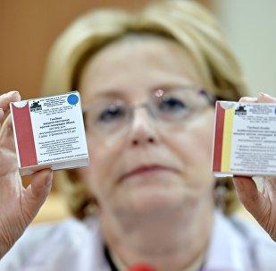A ministra da Saúde da Rússia, Veronika Skvortsova, mostra embalagem de vacina russa contra o ebola