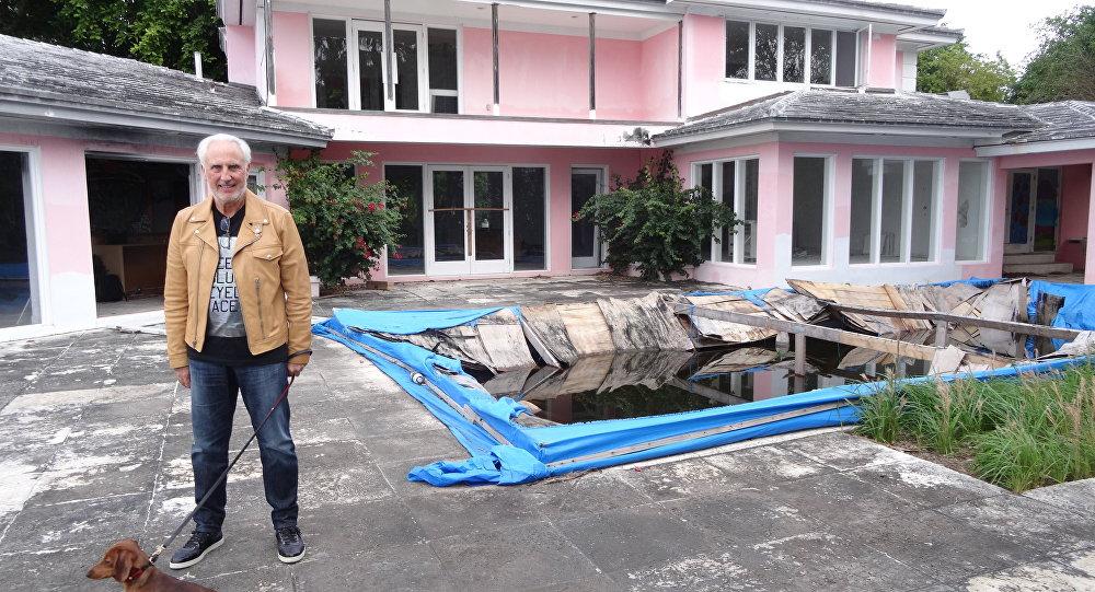 Christian de Berdouare está com seu cão perto da piscina da casa que pertenceu ao notório traficante colombiano Pablo Escobar em 13 de janeiro de 2016 em Miami Beach, FL.