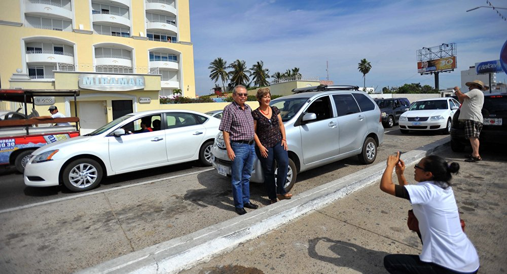 Casal posa para foto em frente ao condomínio Miramar, no México