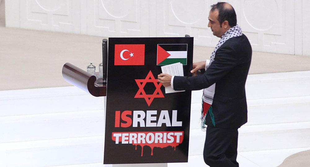 Deputado do Partido de Justiça e Desenvolvimento turco com um keffiyeh palestiniano, coloca o cartaz Isreal Terrorist no parlamento turco, 23 de julho de 2014