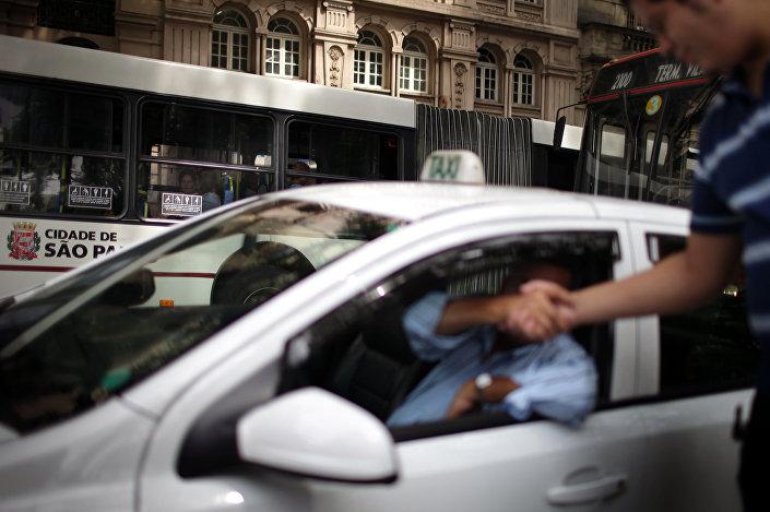 O motorista de um táxi saúda um pedestre perto da praça da Sé, em São Paulo (foto de arquivo)