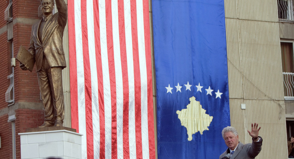 Antigo presidente dos EUA Bill Clinton perto da estátua dele próprio em Pristina, Kosovo, 1 de novembro de 2009