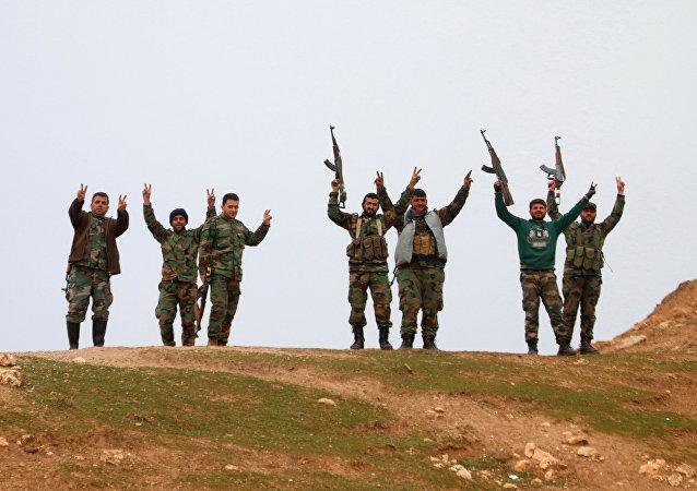 Militares sírios acenam com as mãos após retomar o controle da vila de Kiffin, província de Aleppo, em 11 de fevereiro de 2016